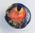 Orange bead fused inside a big holed ugly gray bead. I added dichroic and some clear glass in the later fusings